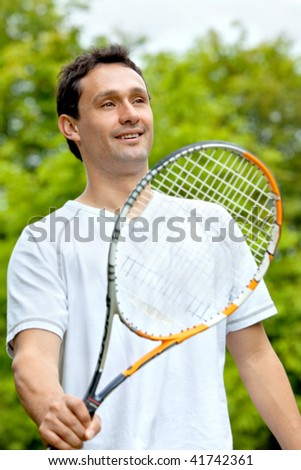 Handsome tennis player holding his racket outside