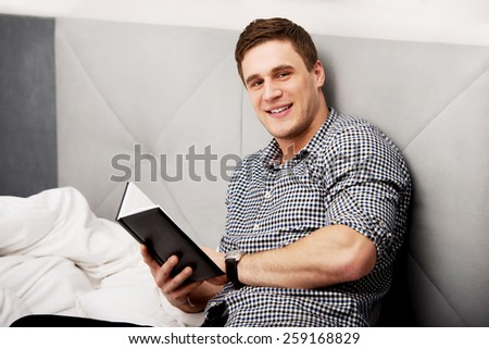 Handsome thoughtful man with a note in his bed. - stock photo