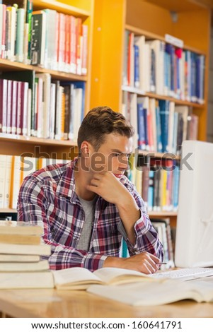 Handsome thoughtful student using computer in library - stock photo
