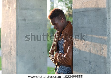 Handsome thoughtful young black man leaning on a wall looking down