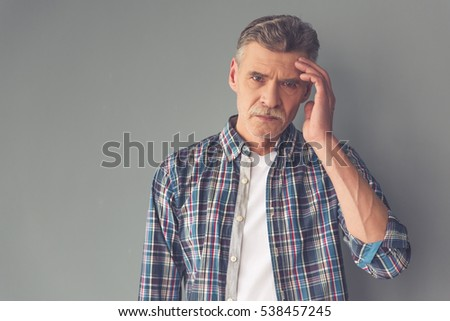 Handsome tired mature man in casual wear is touching his head and looking sadly at camera, on gray background