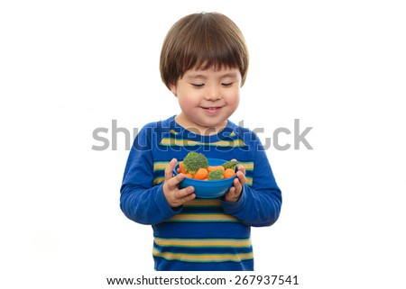 Handsome toddler boy isolated on white background holding blue bowl of fresh vegetables.  Three year old preschooler holding carrots and broccoli, looking down at healthy food, ready to eat nutritious - stock photo