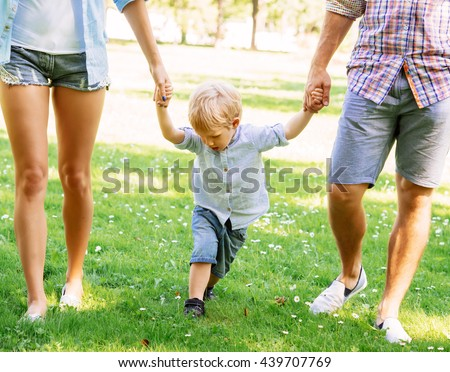 Handsome toddler having a walk with parents holding their hands.