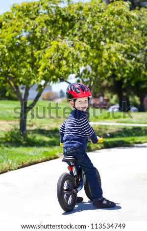 handsome toddler on a balance bike in a park