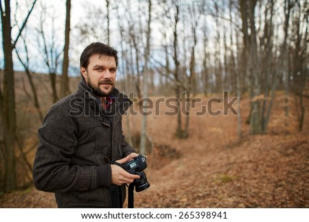 Handsome tourist using digital camera outdoors in a forest on autumn - stock photo