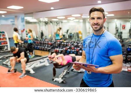 Handsome trainer using tablet in weights room at the gym - stock photo