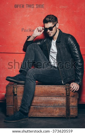 Handsome treasure. Handsome young man adjusting his sunglasses while sitting on wooden chest against red background
