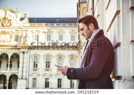 Handsome trendy man wearing dark coat standing and looking down at a cell phone that he is holding, outdoor in European city setting with elegant old historic building behind - stock photo
