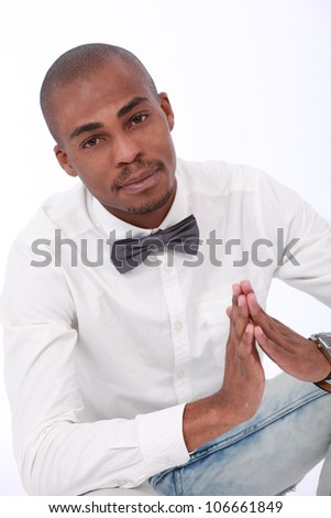 Handsome,Trendy young African American business man or student wearing a long white shirt, jeans and a silver bow tie praying or holding his hands together thoughtfully and content in happiness - stock photo