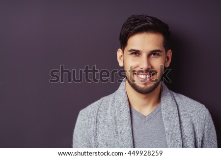 Handsome trendy young bearded man with a friendly smile standing against a dark background looking at the camera, head and shoulders with copy space