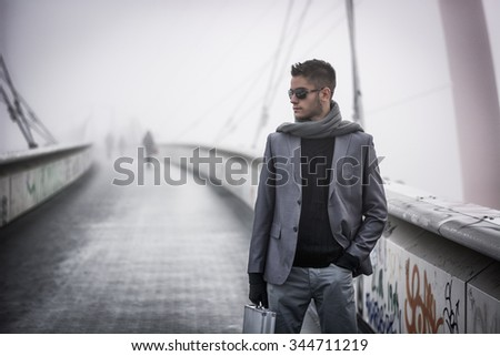Handsome trendy young man walking on a bridge in winter, carrying a metal briefcase, wearing sunglasses and scarf in a foggy day - stock photo