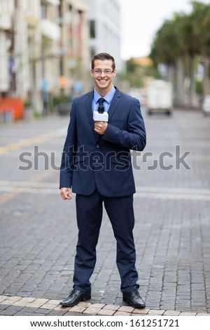 handsome tv journalist reporting from urban street - stock photo