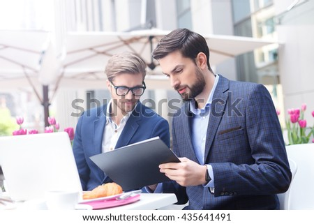 Handsome two businessmen are working in cooperation - stock photo