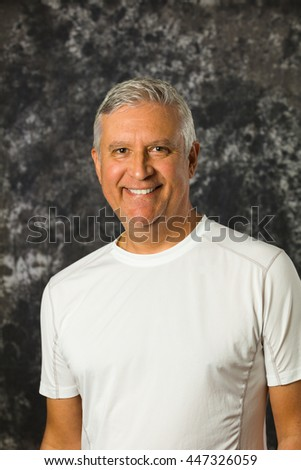 Handsome unshaven middle age man studio portrait with a gray background.