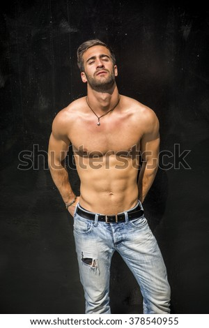 Handsome unshaven shirtless young man standing against black wall, looking at camera - stock photo