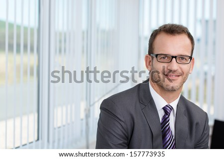 Handsome unshaven young businessman wearing glasses and a suit standing in his office in front of a window overlooking a rural view - stock photo