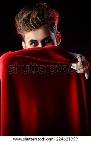 Handsome vampire hiding his face behind his cloak. Halloween. Dracula costume. - stock photo