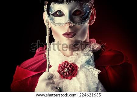 Handsome vampire wearing venetian mask. Halloween carnival. Dracula costume. - stock photo