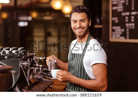 Handsome waiter adding milk to coffee at the cafe - stock photo