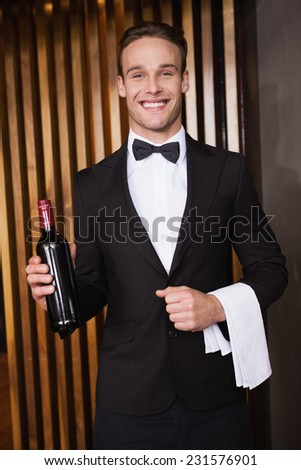 Handsome waiter holding a bottle of red wine and a towel in a bar