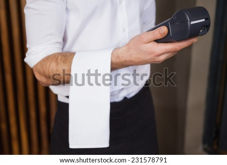 Handsome waiter holding credit card machine in a bar - stock photo