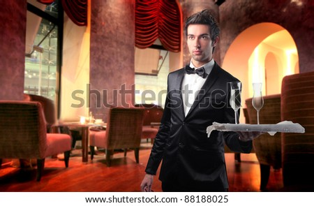 Handsome waiter serving wine glasses in a lounge bar - stock photo