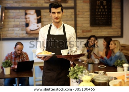 Handsome waiter working in cafeteria, holding trays in both hands, looking at camera,