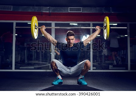 Handsome weightlifter preparing for training. Shallow depth of field. - stock photo
