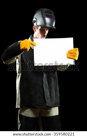 handsome welder holding a blank form. isolated on black background - stock photo