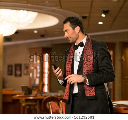 Handsome well-dressed brunette  in luxury interior with mobile phone - stock photo