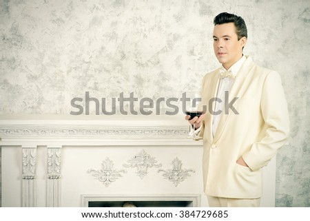 Handsome well-dressed mature man in elegant white suit stands by the fireplace. - stock photo