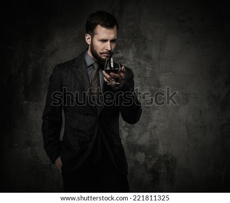 Handsome well-dressed with glass of beverage  - stock photo