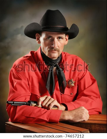 handsome Western cowboy with gun and badge sitting in studio - stock photo