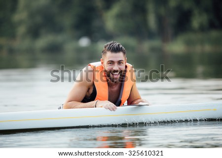 handsome wet man standing in water and smiling on a paddle board surrounded by trees - stock photo