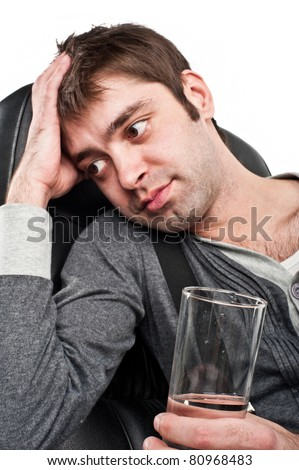 handsome white guy sitting on a Caucasian black chair in the gray jacket and a sad expression on his face holding a glass of mineral water isolated over white - stock photo