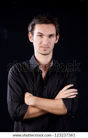 Handsome white man in black shirt with arms crossed and looking at the camera with thoughtful, focused expression