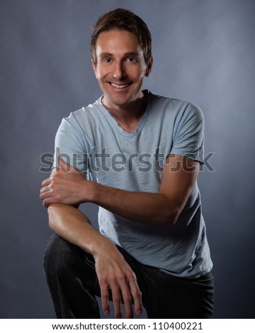 Handsome white man photographed in studio on a gray background wearing a modern blue t shirt and jeans.