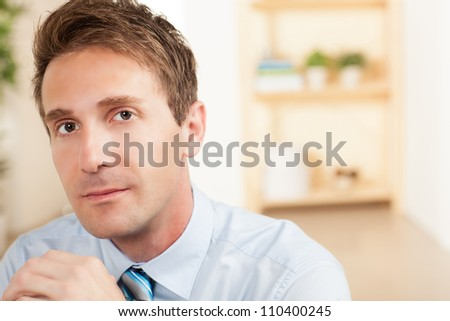 Handsome white professional at work wearing a blue shirt and tie. - stock photo