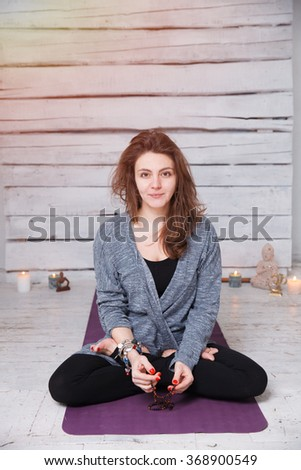 Handsome woman having yoga meditation practice on violet gymnastic carpet in white lit room with candles. She has long hair, black sport suit and ethnic accessories. - stock photo