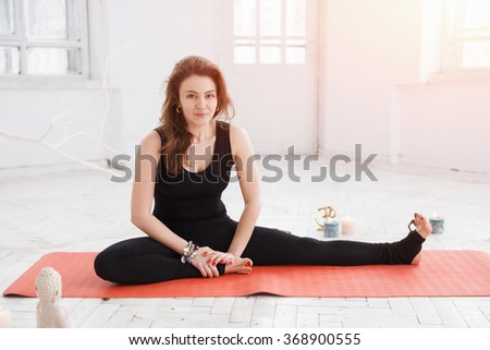 Handsome woman having yoga practice on red gymnastic carpet in white lit room. She has long hair, black sport suit and ethnic accessories. - stock photo