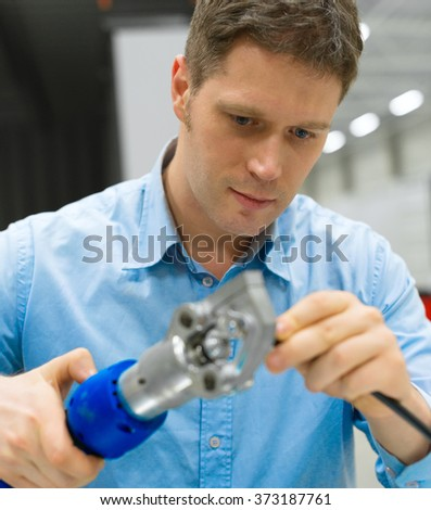 Handsome worker compressing cable connector at the factory. - stock photo