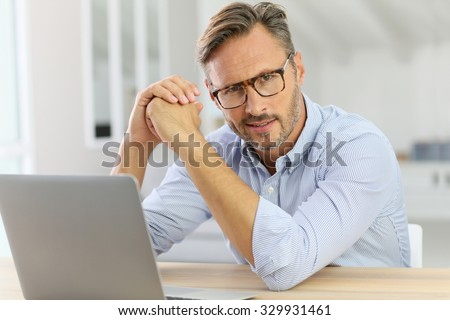 Handsome 40-year-old man at home using laptop - stock photo