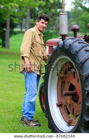 Handsome 50 year old Man next to a Vintage tractor - stock photo