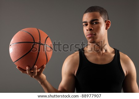 Handsome young african american sportsman showing off fit biceps in black vest holding basketball in one hand, shot against grey background. - stock photo