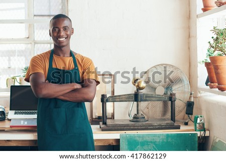 Handsome young African artisan smiling confidently in beautifull studio - stock photo
