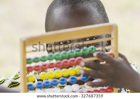 Handsome Young African Black Boy Playing with an Abacus School. Back to School symbol: young black boy playing with an abacus toy at school. handsome little man learning to count using a known game. - stock photo