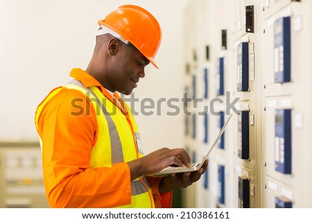handsome young african control room engineer using laptop - stock photo