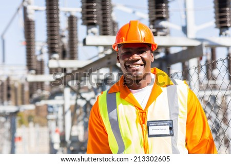 handsome young african electrical engineer at substation - stock photo