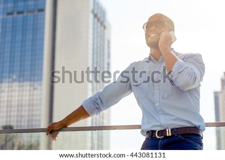 Handsome young Afro American businessman in sun glasses is talking on the mobile phone and smiling while standing outdoors - stock photo