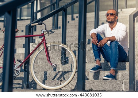 Handsome young Afro American man in casual wear and sun glasses is looking away and thinking while sitting on stairs outdoors - stock photo